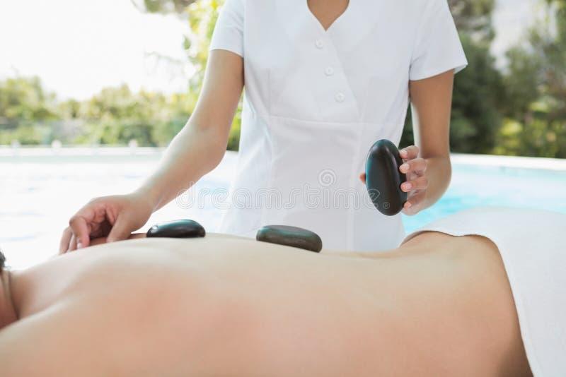 Средний раздел человека получая каменный массаж на спа-центре стоковое изображение rf