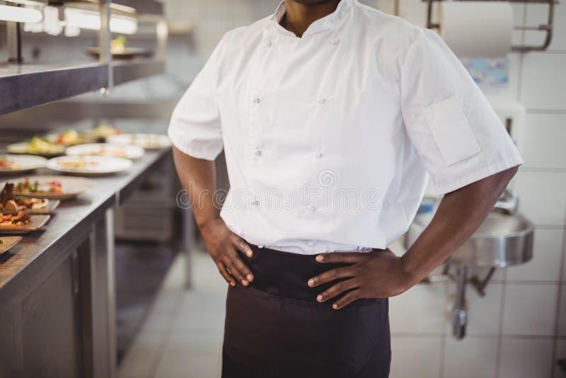 Средний раздел шеф-повара стоя с руками на бедре в коммерчески кухне стоковые фото