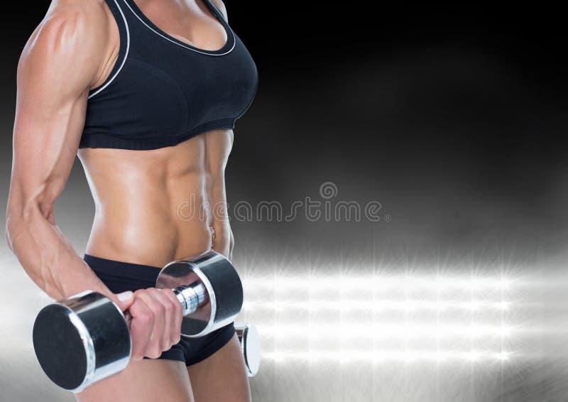 Средний-раздел dumbell мышечной женщины поднимаясь против яркого света стоковое изображение