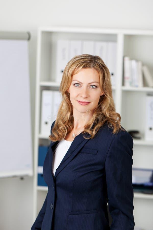 Средняя взрослая коммерсантка в офисе стоковое изображение