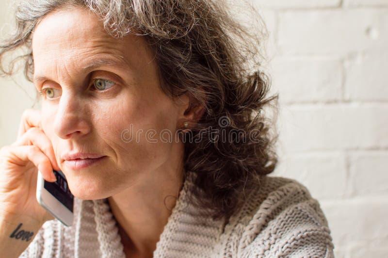 Средняя постаретая женщина говоря на телефоне стоковое изображение