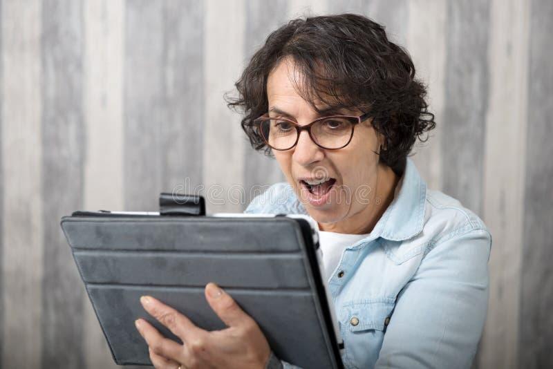Средн-постаретая женщина звоня дистантный на интернете стоковое изображение