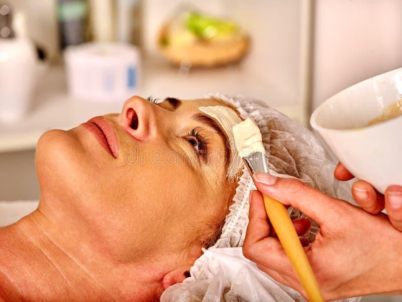 Средн-постаретая женщина получает массаж стороны в салоне курорта стоковые изображения