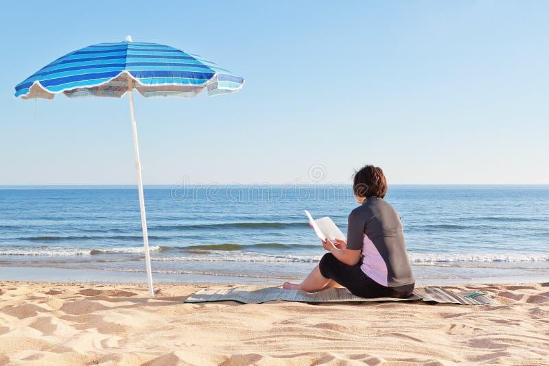 Средн-постаретая женщина сидя на пляже читая книгу. стоковое фото