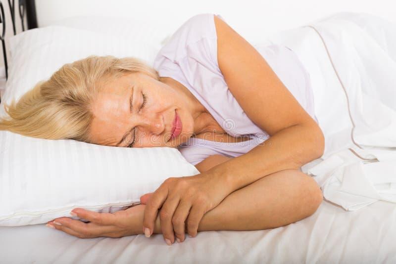 Средн-постаретая женщина спать в кровати стоковые фотографии rf