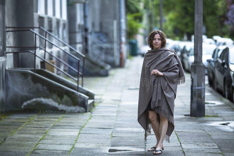 Средн-постаретая женщина стоя на улице стоковые фото