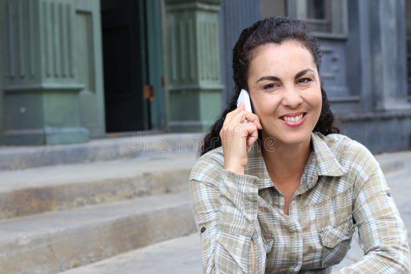 Средн-постаретая счастливая excited смеясь над женщина говоря на предпосылке города мобильного телефона outdoors городской стоковая фотография
