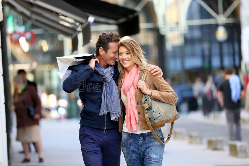 Средн-постаретые пары вися вне в ходить по магазинам улиц стоковая фотография