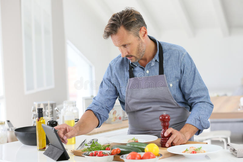 Средн-постаретый человек варя в кухне стоковое фото rf