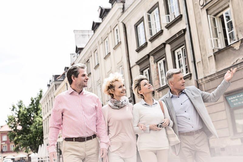 Средн-постаретый человек показывая что-то к друзьям пока идущ в городе стоковые фотографии rf