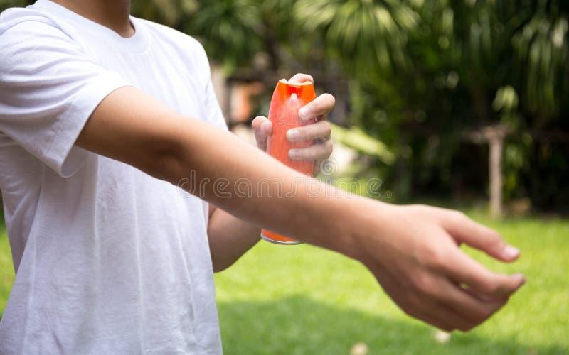 Средства от насекомых молодого мальчика распыляя на коже с бутылкой брызга стоковые изображения