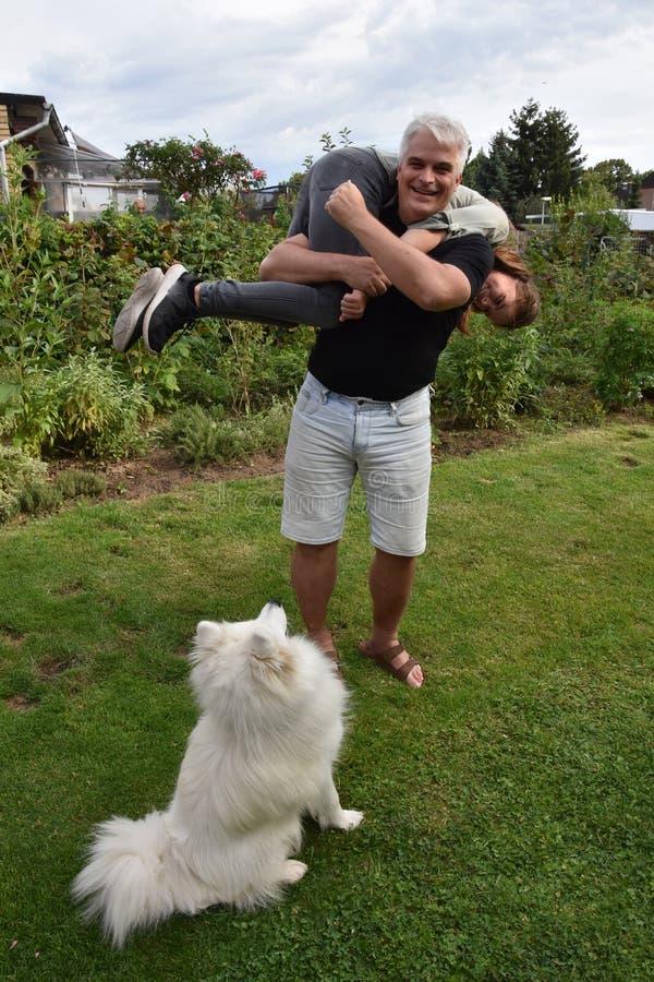Ссорясь отец и дочь, собака наблюдают удивленный стоковые фотографии rf