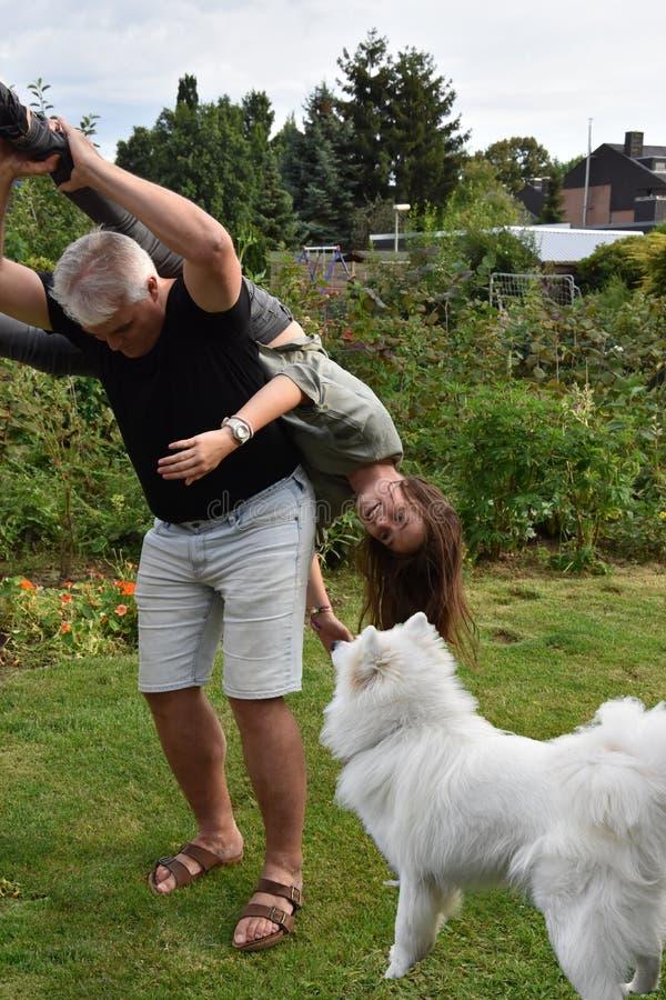 Ссорясь отец и дочь, собака наблюдают удивленный стоковая фотография rf