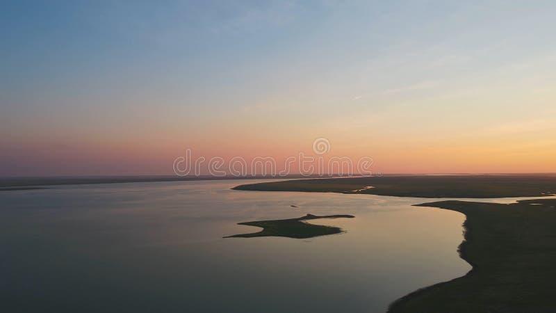 Стадо птиц на предпосылке красочного неба Заход солнца на реке Остров чаек Птицы летают на заход солнца, воздушный стоковые фото