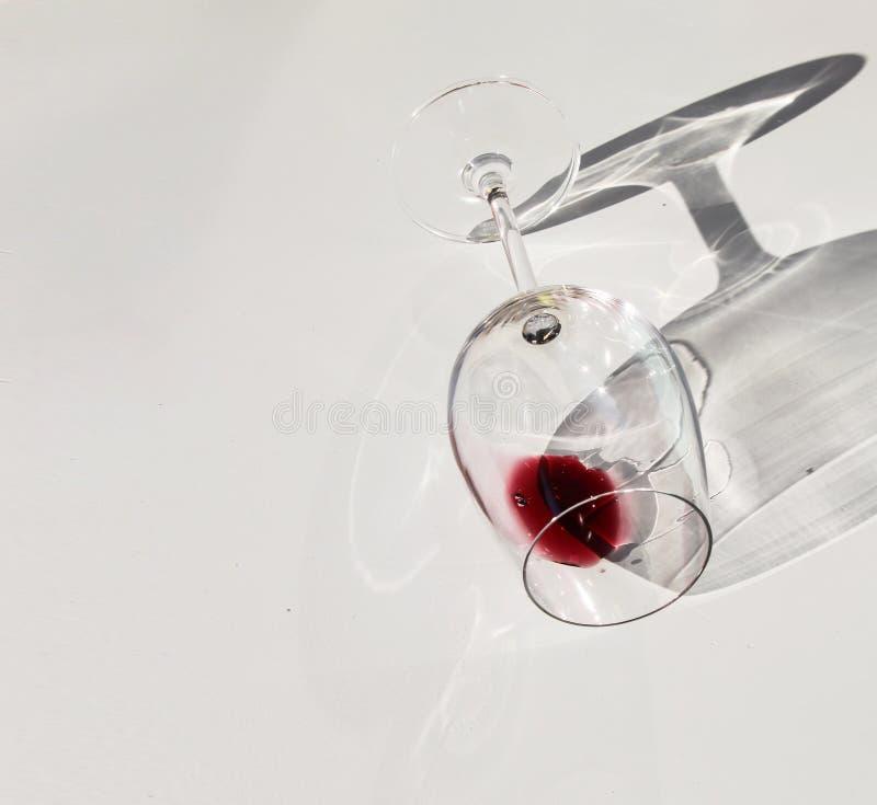 Стакан, наполненный красным вином, лежащим на белом столе стоковое фото