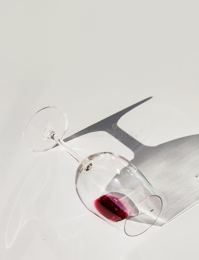 Стакан, наполненный красным вином, лежащим на белом столе стоковое фото rf