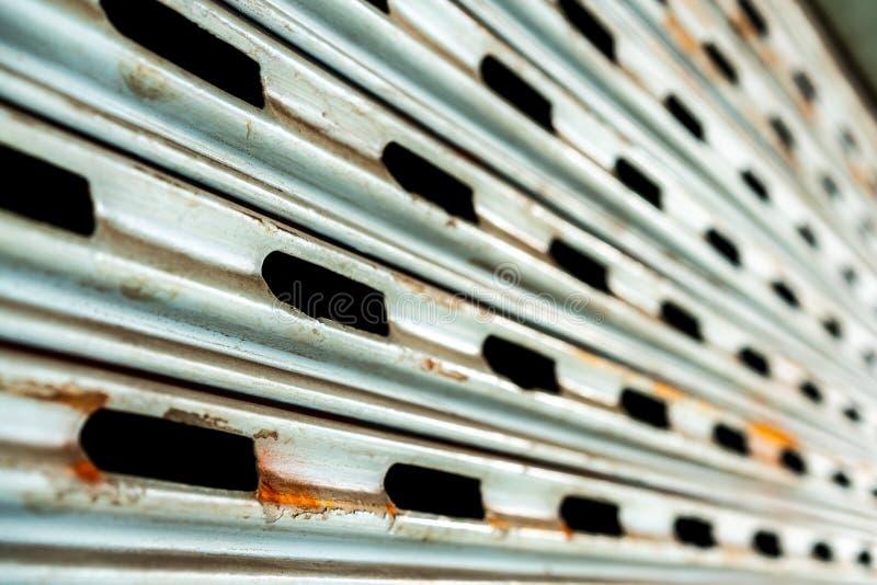 Стальная деревенская винтажная свертывая дверь с отверстиями Деревенская текстура двери шторки стоковая фотография rf