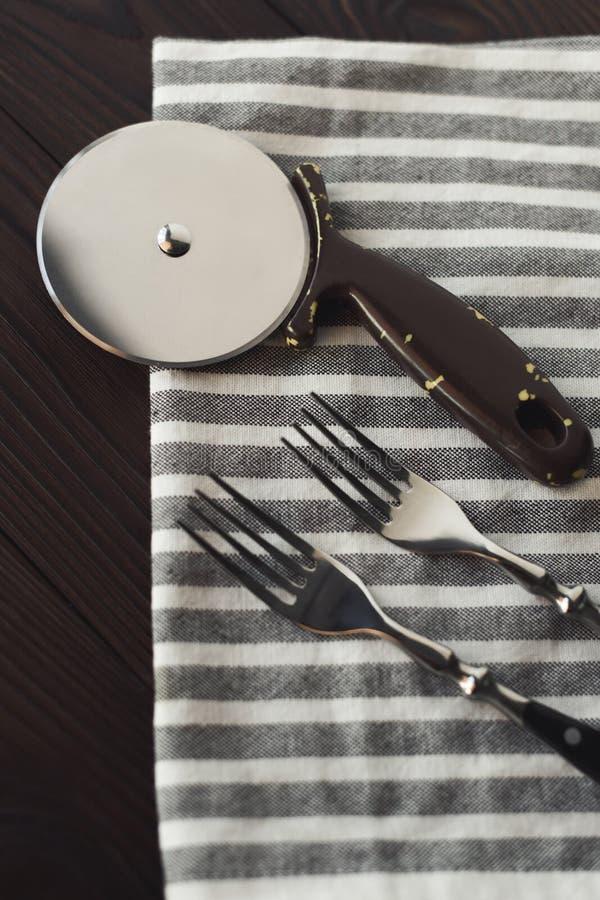 Стальные вилки и резец пиццы на linen салфетке стоковые фото