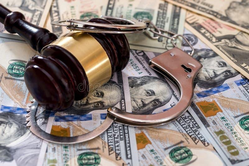 Стальные наручники с молотком судьи на банкнотах доллара стоковая фотография
