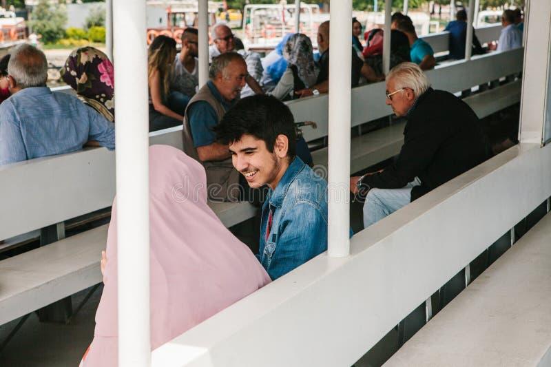 Стамбул, 17-ое июня 2017: Молодая пара плавания человека и женщины на шлюпке парома или пассажира и говорить, он усмехается стоковое изображение