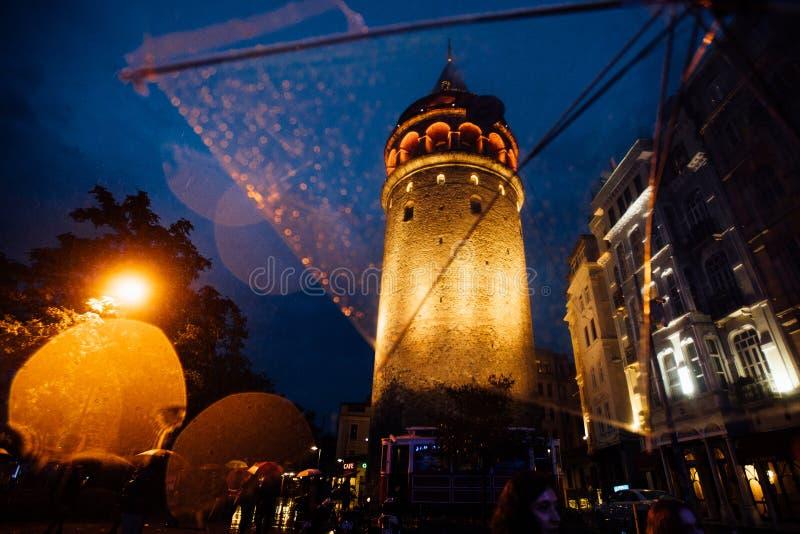 Стамбул, башня Galata Взгляд на архитектуре через прозрачный зонтик в дожде Славное bokeh Туризм стоковая фотография rf