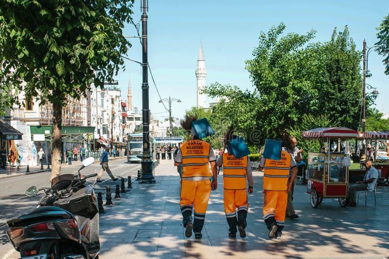 Стамбул, 15-ое июня 2017: 3 привратника улицы в ярких оранжевых формах идут вниз с улицы держа веники и стоковые изображения rf