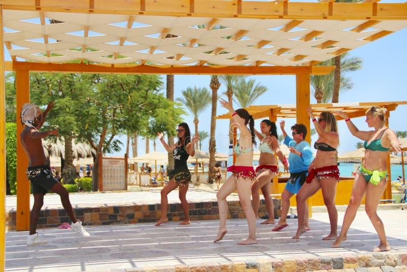 Станцуйте девушки инструктора уча для того чтобы станцевать передвижной танец Женская команда танцуя совместно стоковые изображения
