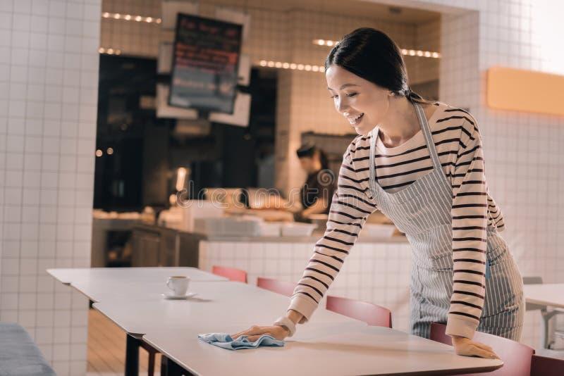 Старательная профессиональная официантка очищая таблицу в утре стоковые фотографии rf