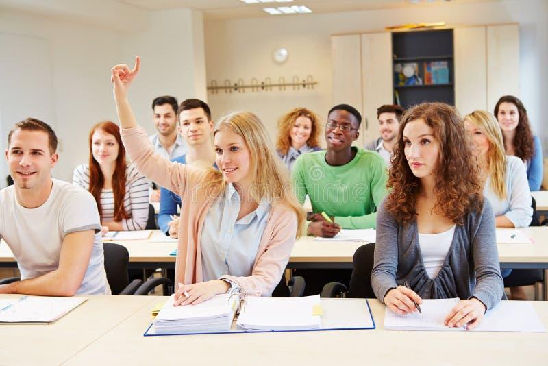 Рука женского студента поднимаясь стоковое изображение