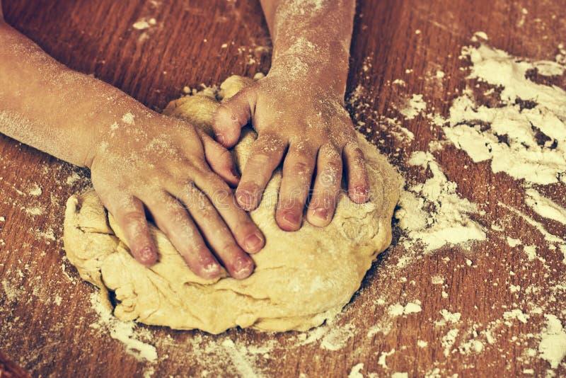 Старательно руки детей делают тесто. стоковая фотография