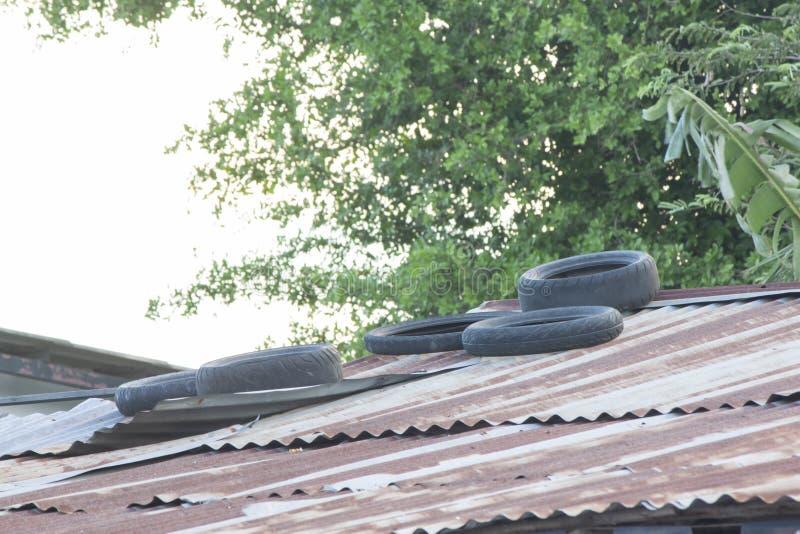Старая автошина помещена на крыше цинка для предотвращения цинка от дунутый отсутствующий штормом стоковые фотографии rf