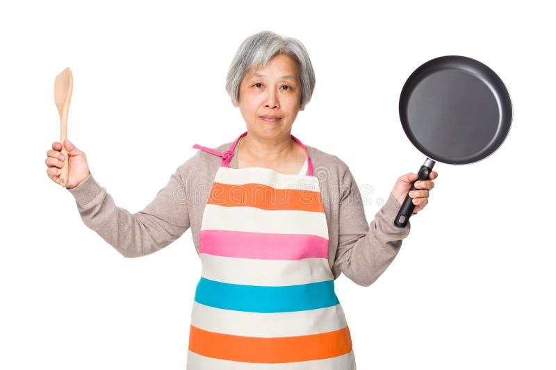 Старая азиатская домохозяйка задерживая деревянные ковш и сковороду стоковая фотография rf