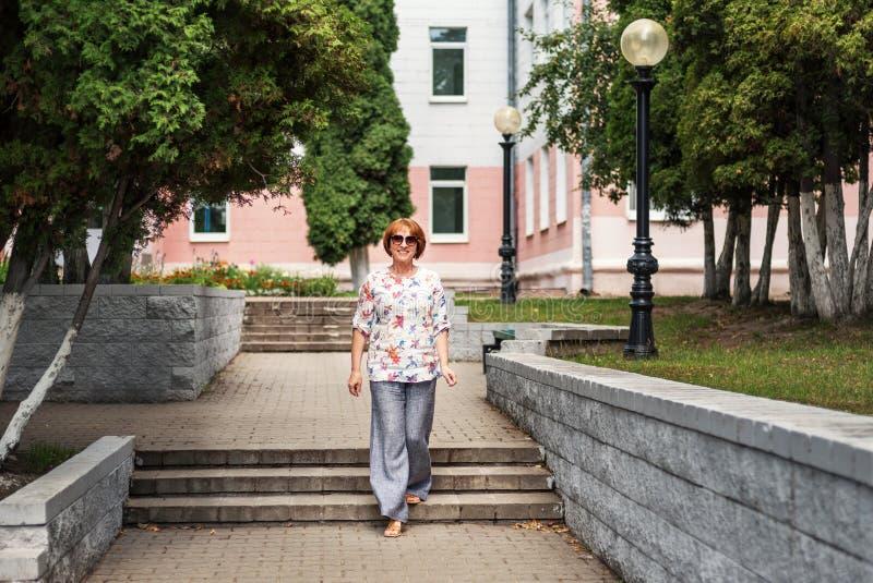 старая активная женщина юрко идет вдоль улицы и улыбок города счастливо в солнечные очки и linen одежды стоковое изображение
