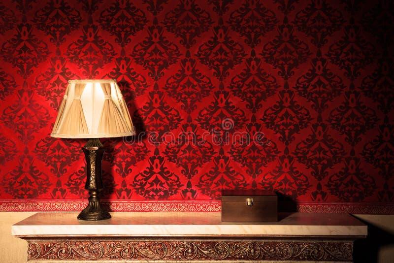 Старая лампа в винтажном интерьере рядом с деревянной коробкой стоковое изображение