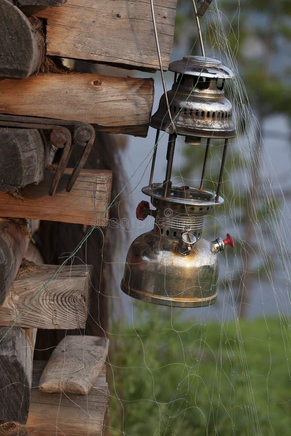 Старая лампа керосина на деревянной рамке и рыболовной сети стоковое фото rf
