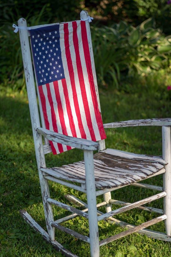 Старая белая деревенская кресло-качалка с флагом Соединенных Штатов стоковые фотографии rf