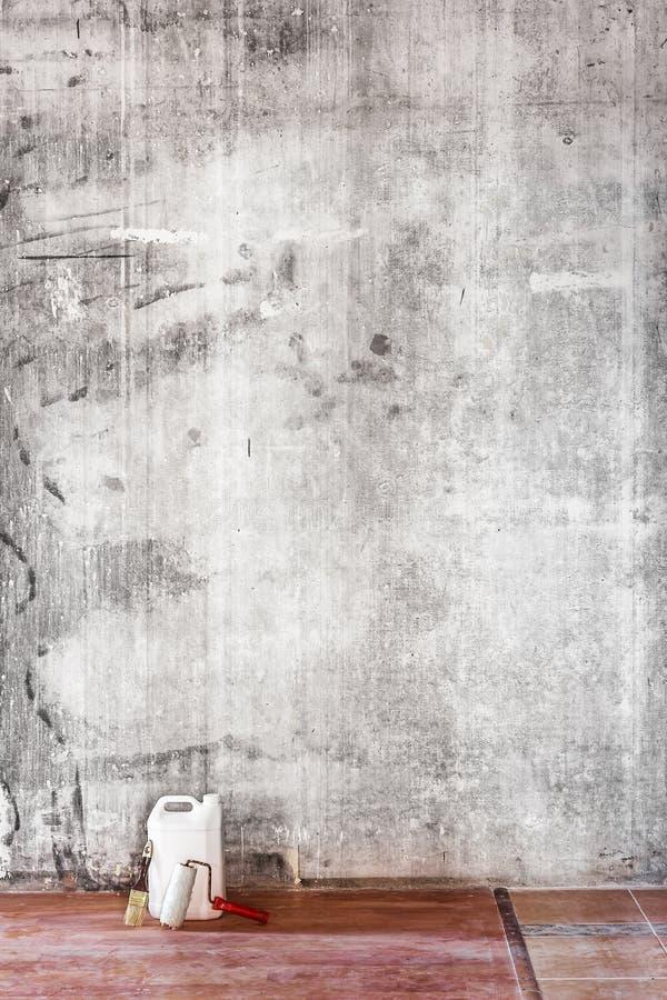Старая бетонная стена в ремонтировать комнату, пакостный коричневый пол и инструменты стоковые фото
