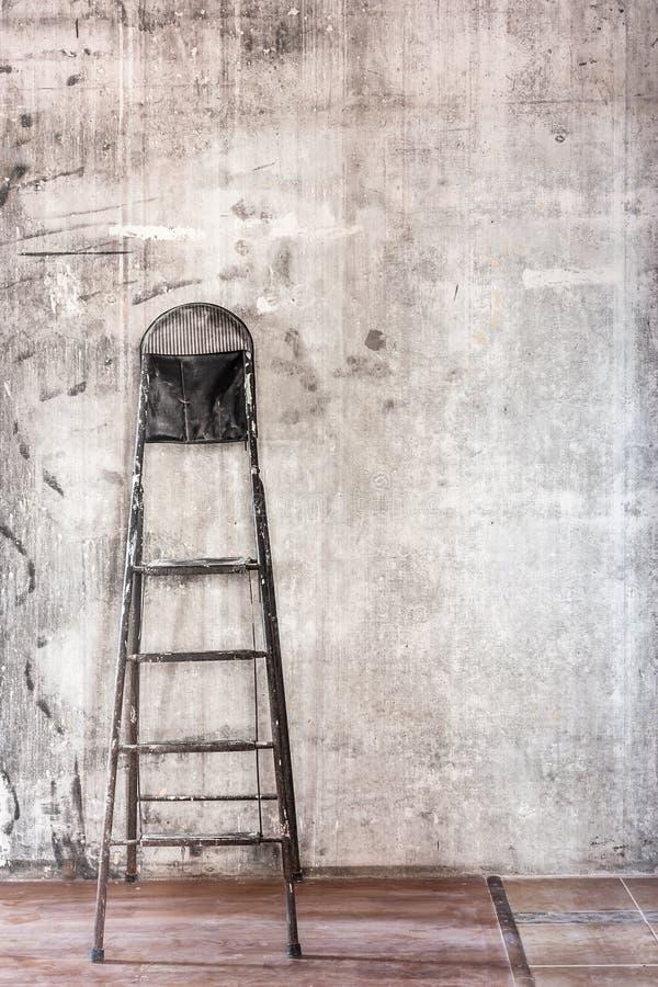 Старая бетонная стена в ремонтировать комнату с пакостными полом и steplad стоковое изображение