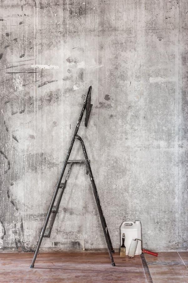 Старая бетонная стена в ремонтировать комнату с пакостными полом, инструментами и s стоковое изображение rf