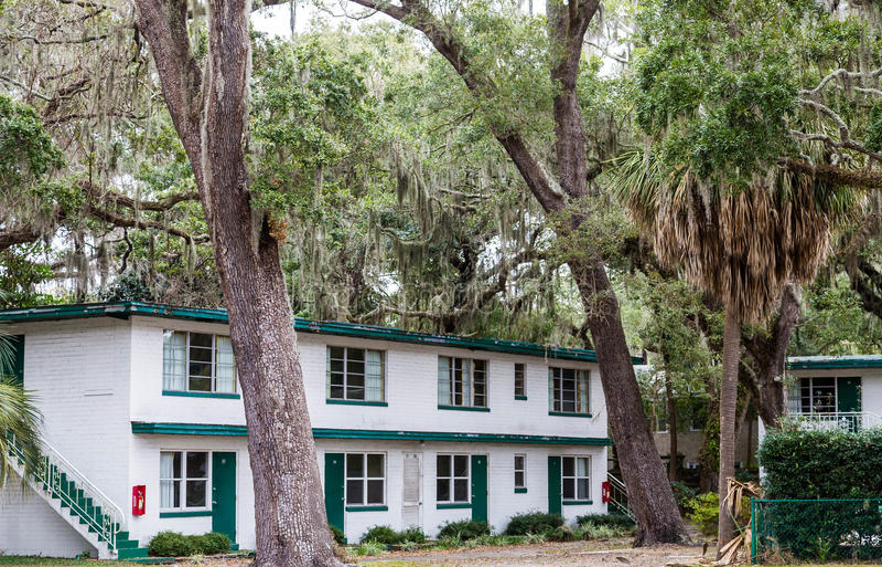 Старая белая и зеленая гостиница за дубами стоковая фотография rf