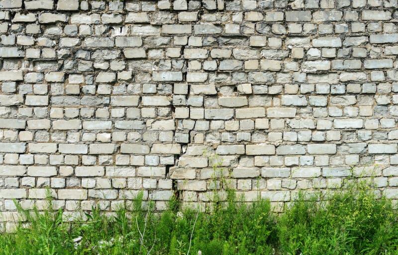 Старая белая кирпичная стена с великолепной и зеленой травой стоковые изображения