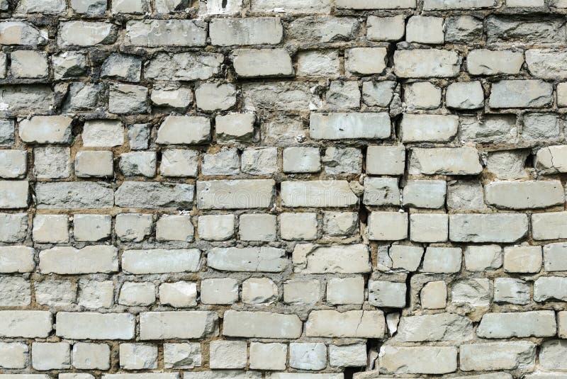Старая белая кирпичная стена с расселиной стоковые изображения