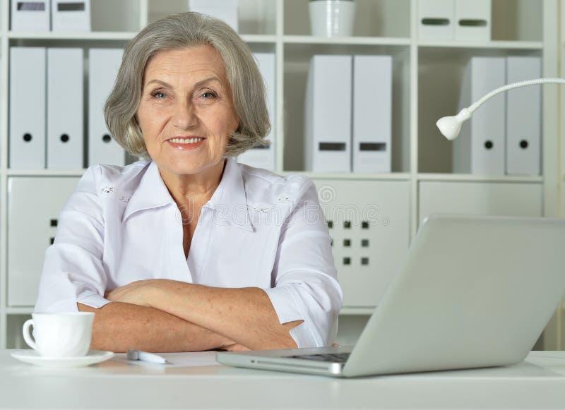 Старая бизнес-леди с деятельностью компьтер-книжки стоковые фото