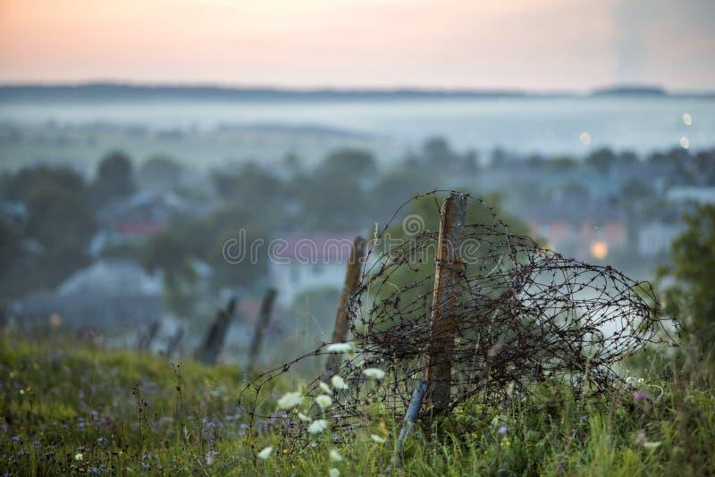 Старая большая колючая проволока свернулась спиралью на ржавом поляке, сломанной загородке сада дальше стоковое фото