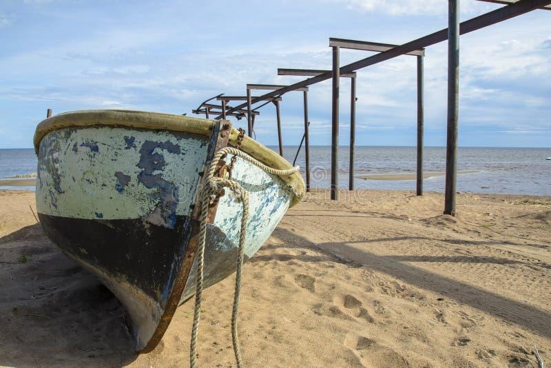 Старая большая рыбацкая лодка на предпосылке моря, песка и сломленного моста Telfer для запуская шлюпок в старой рыбной ловле стоковые изображения