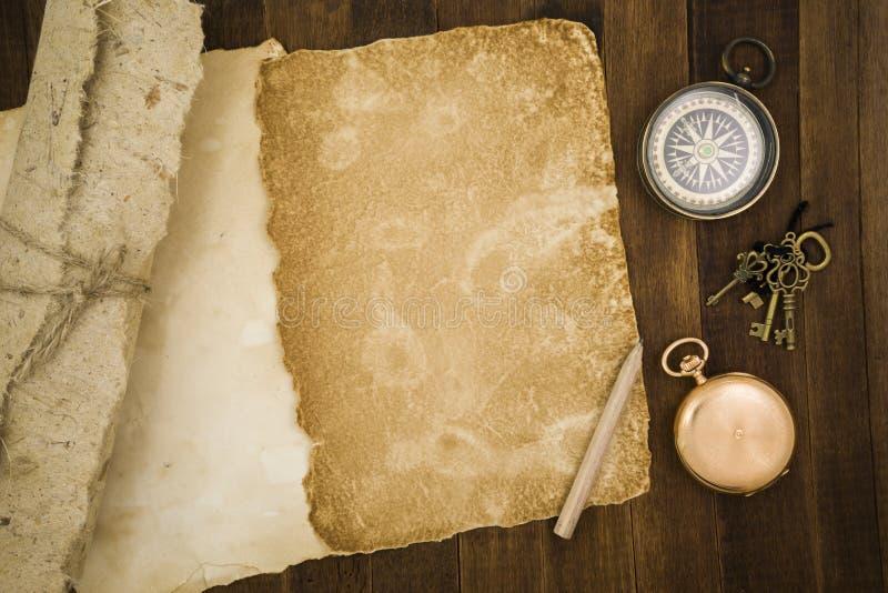Старая бумага, компас, карманный вахта на деревянной предпосылке стоковые изображения