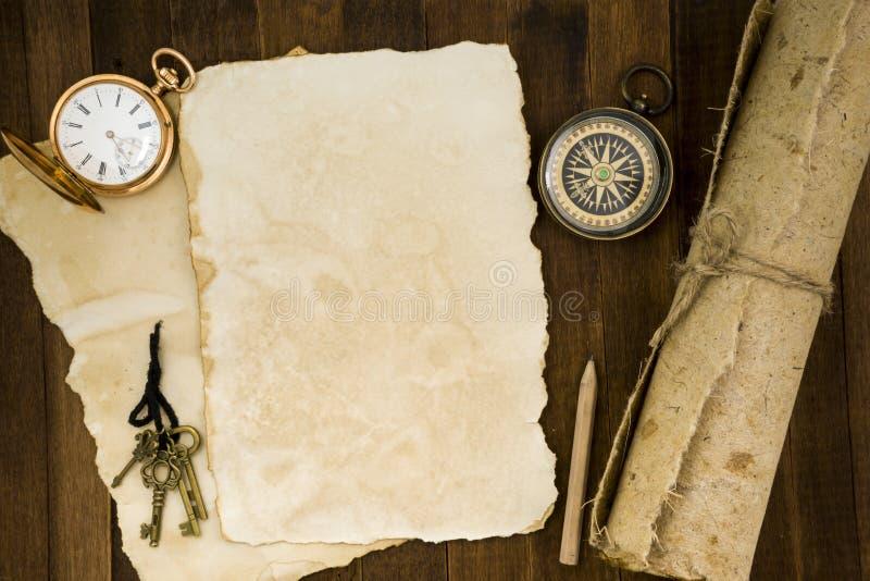 Старая бумага, компас, карманный вахта на деревянной предпосылке стоковое фото