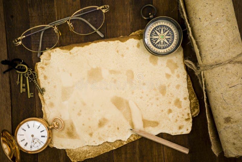 Старая бумага, компас, карманный вахта на деревянной предпосылке стоковая фотография