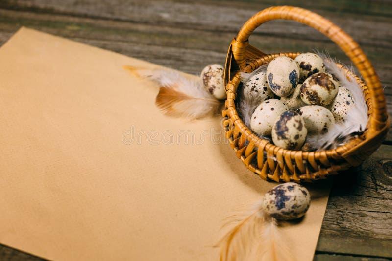 Старая бумага с яичками внутри меньшей корзины с яичками триперсток на деревенской деревянной предпосылке Насмешка года сбора вин стоковые фото