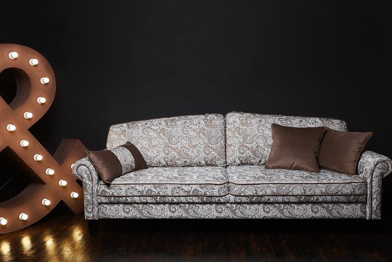 Старая введенная в моду бежевая софа с картинами на интерьере просторной квартиры, стойками на деревянном поле на темной предпосы стоковая фотография